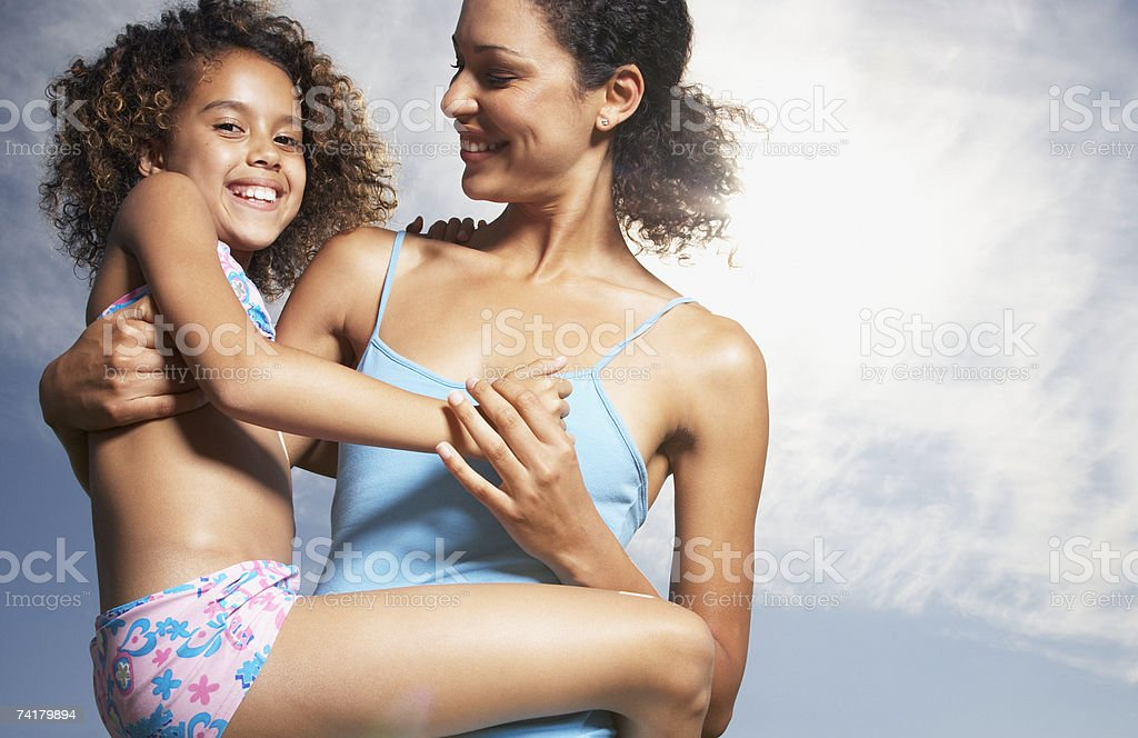Woman and girl in swimsuit playing outdoors royalty-free stock photo