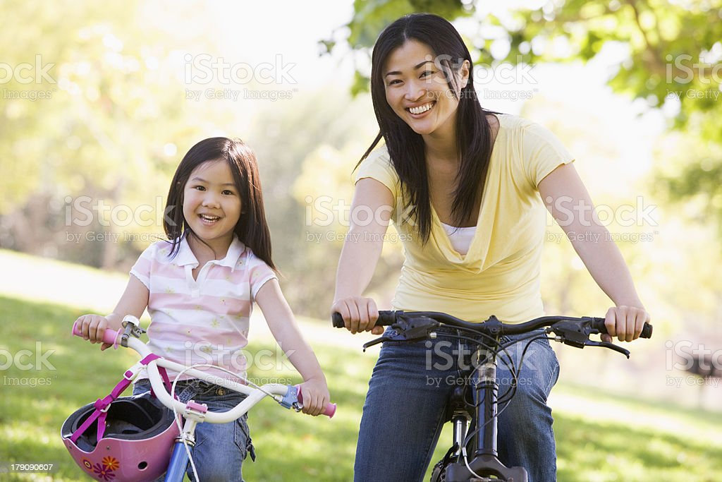 Woman and girl riding a bike in the park stock photo