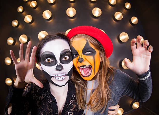 woman and girl with painted faces. halloween theme - plants of zombies stock-fotos und bilder