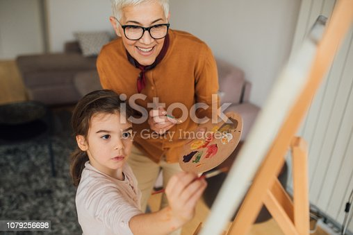Happy grandmother and a girl painting