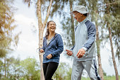 istock A woman and grandfather are walking jogging on the street at the park. Grandfather talk about the story of  past life experiences. Healthy and lifestyle concept. 1289036691