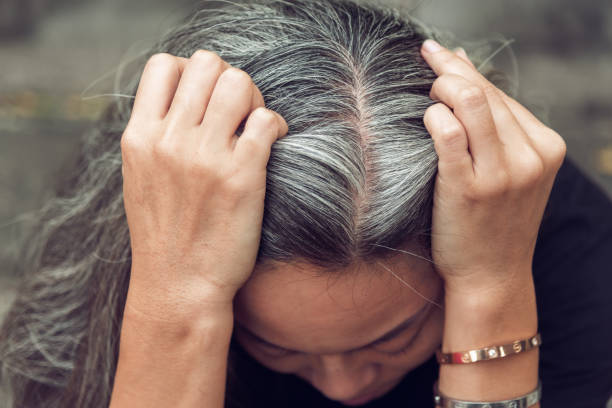 woman and gray hair with worried stressed face looking down stock photo