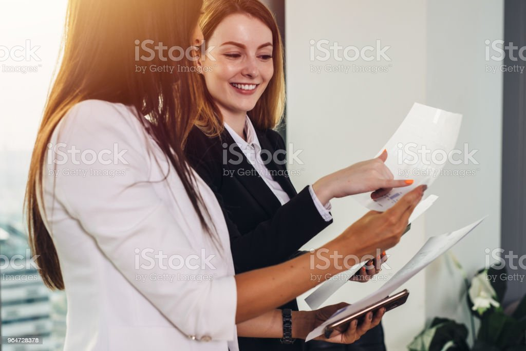 Woman and her assistant holding documents discussing business plan and strategy at workplace royalty-free stock photo