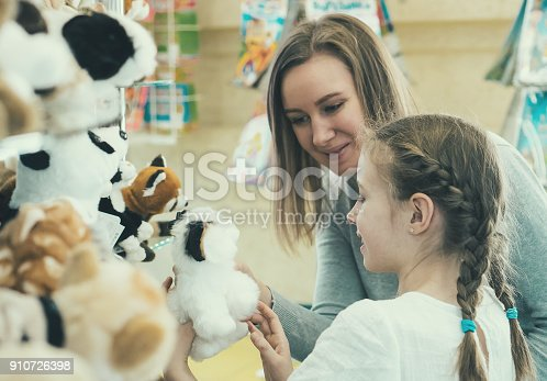 Woman and her daughter choosing toy in kids store.