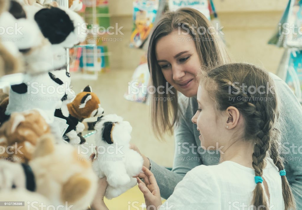 Woman and her daughter choosing toy in kids store. stock photo