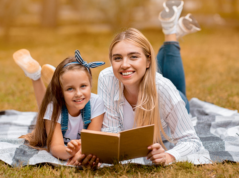 istock Woman And Her Daughter Reading Book In Countryside In Autumn 1264233442