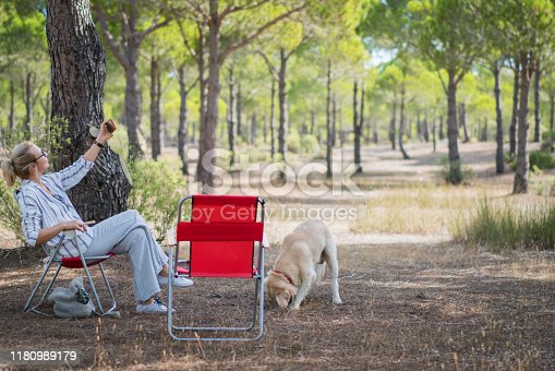636418612 istock photo Woman and her dog camping in forest and doing selfie. 1180989179