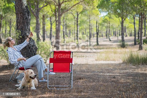 636418612 istock photo Woman and her dog camping in forest and doing selfie. 1180989281