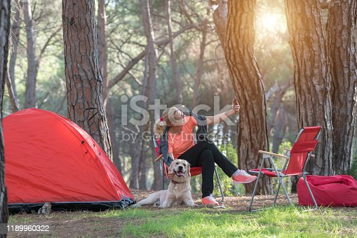 636418612 istock photo Woman and her dog camping in forest 1189960322