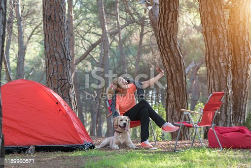 636418612 istock photo Woman and her dog camping in forest 1189960571