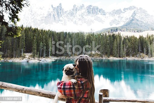 Young woman in sunglasses and red flannel shirt and her small fluffy pug having fun near beautiful turquoise mountain lake, pine forest and the Alps in Italy
