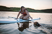 Latino woman paddleboarding with her little dog and having fun at sunset.