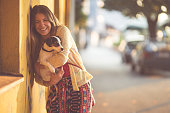 Young woman holding her little dog in her arms while walking through the city