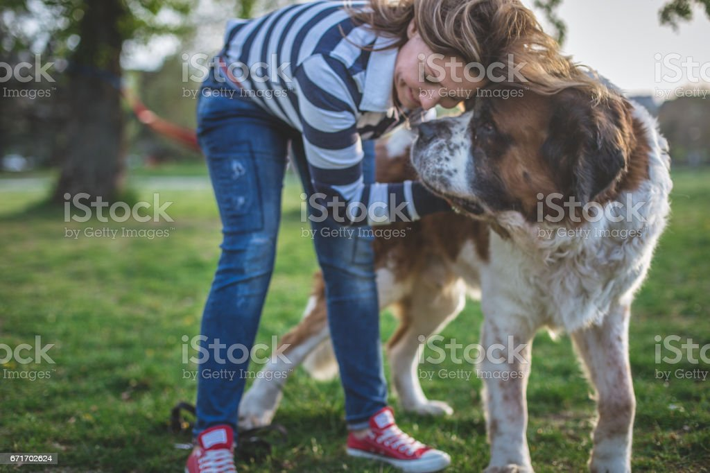 Woman and her dog, pressing forehead to forehead stock photo