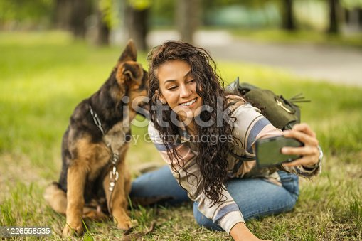636418612 istock photo Woman and her dog taking a selfie by mobile phone 1226558535