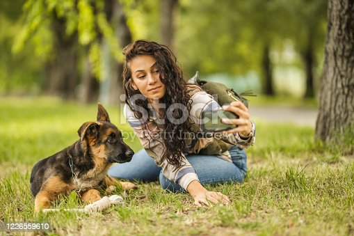 636418612 istock photo Woman and her dog taking a selfie by mobile phone 1226559610