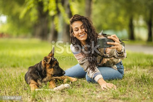 636418612 istock photo Woman and her dog taking a selfie by mobile phone 1226561022
