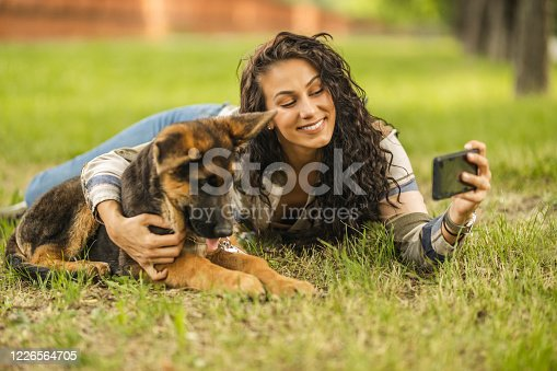 636418612 istock photo Woman and her dog taking a selfie by mobile phone 1226564705