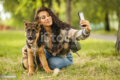 636418612 istock photo Woman and her dog taking a selfie by mobile phone 1226565887