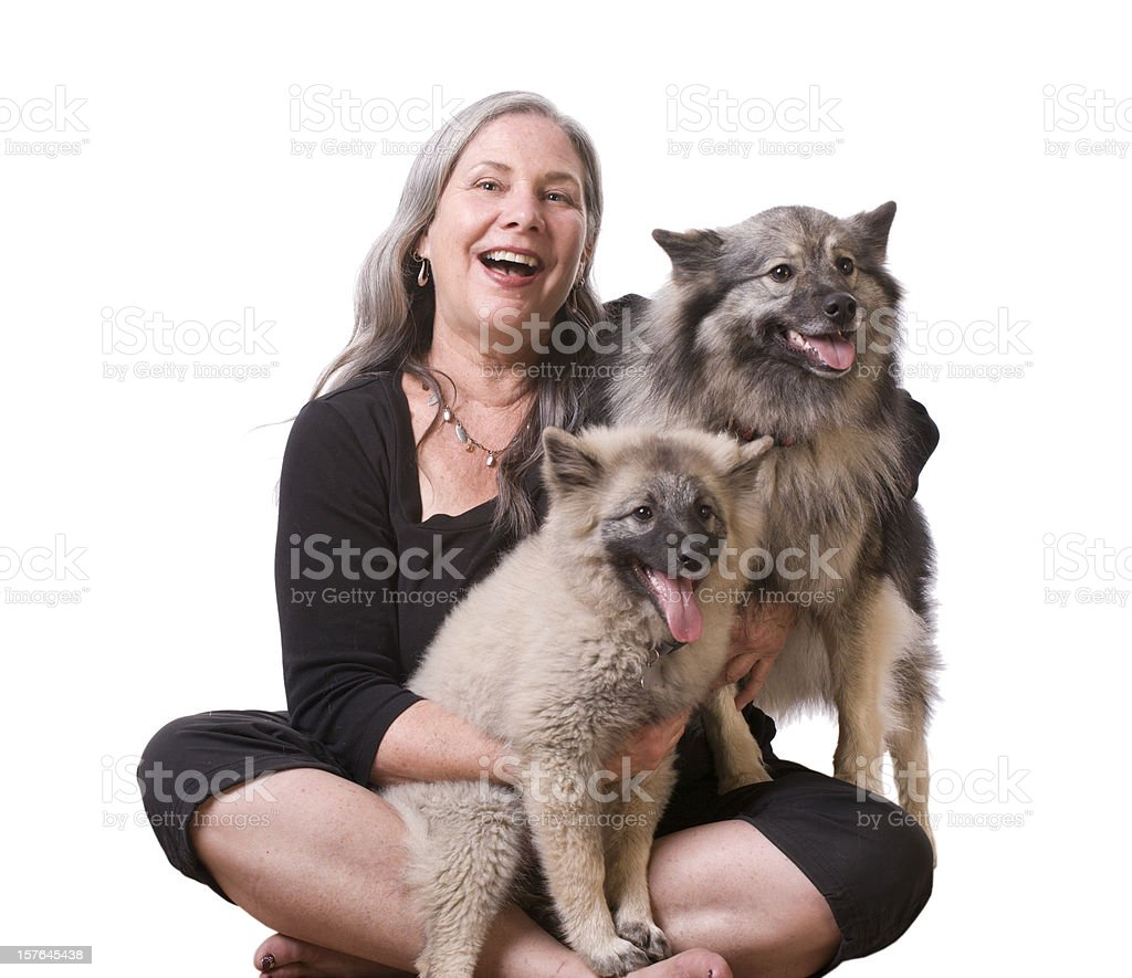 Woman and her Keeshond dogs stock photo