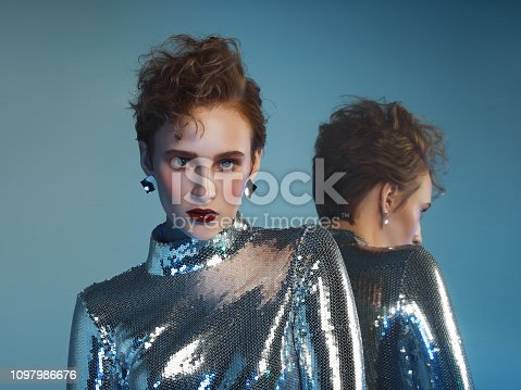 Woman in futuristic sequin jumpsuit and her mirror reflection