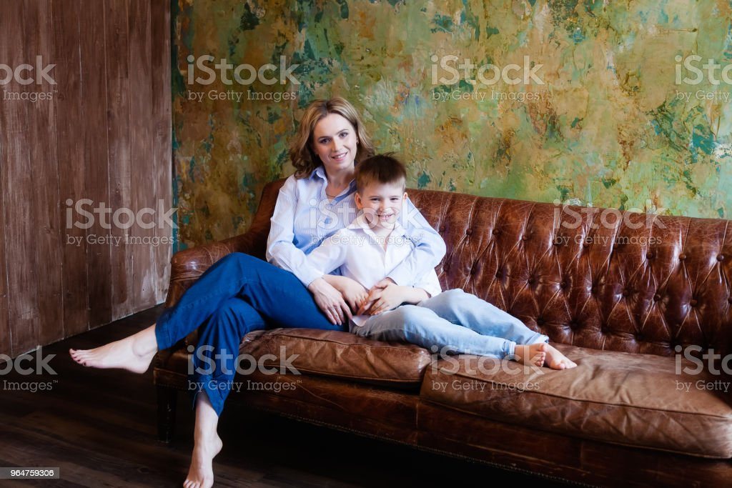 A woman and her son are sitting on the couch in the room, they are looking at the camera and smiling royalty-free stock photo