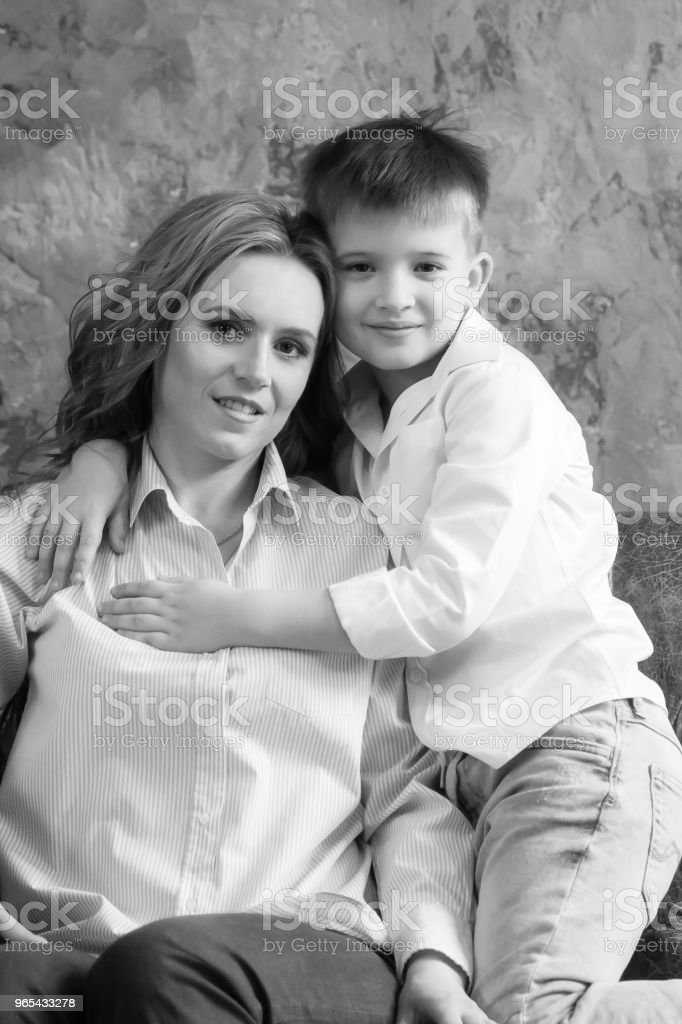 A woman and her son are sitting on the couch in the room, they are looking at the camera and smiling zbiór zdjęć royalty-free