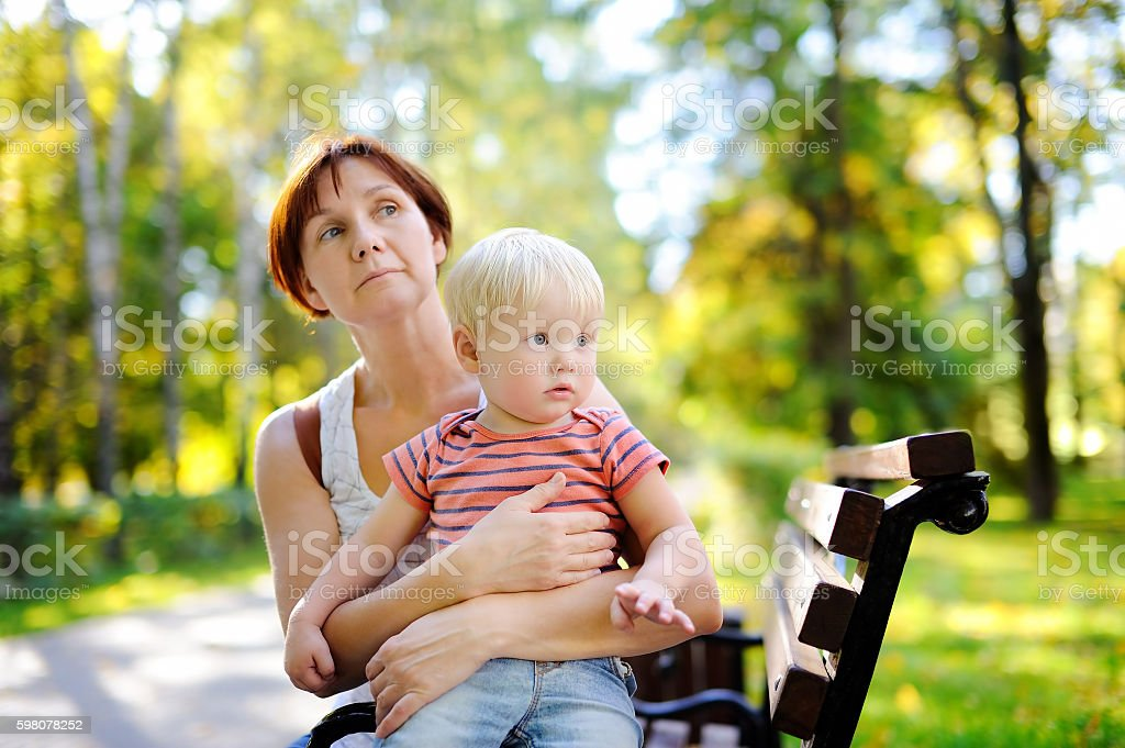 Woman and her toddler grandson enjoy sunny autumn day - foto de stock