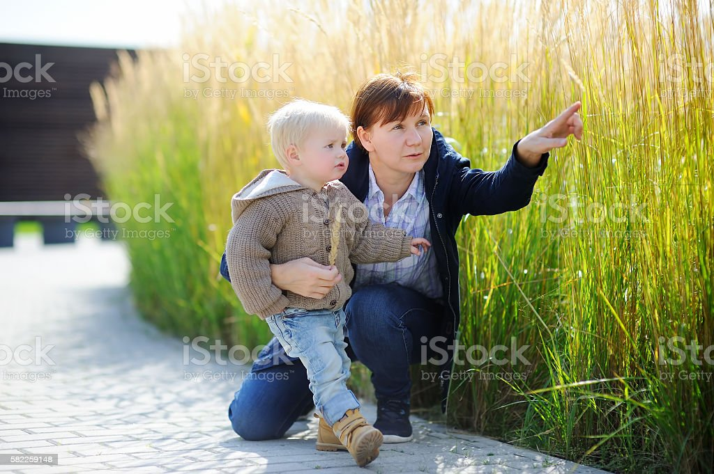 Woman and her toddler grandson playing outdoors - foto de stock