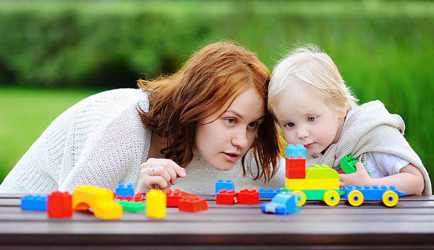 Woman and his son playing with colorful plastic blocks - foto de stock