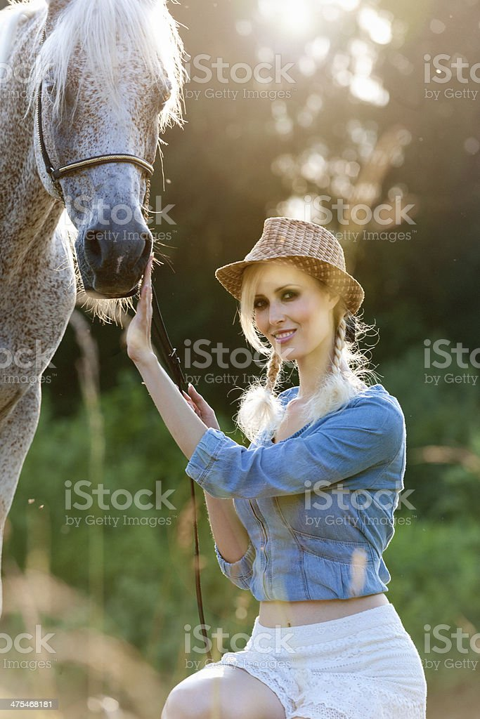 woman and horse in meadow in summer royalty-free stock photo
