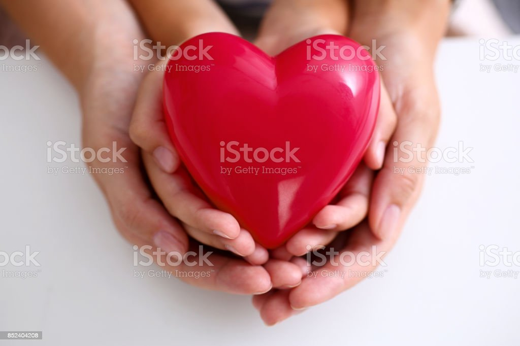 Woman and kid hold red toy heart in arms - foto stock