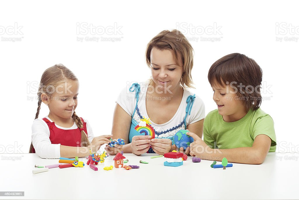 Woman and kids playing with colorful clay stock photo