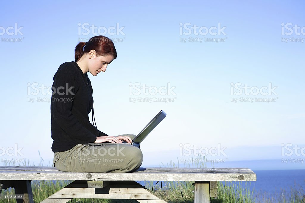 Woman and laptop on the shore royalty-free stock photo