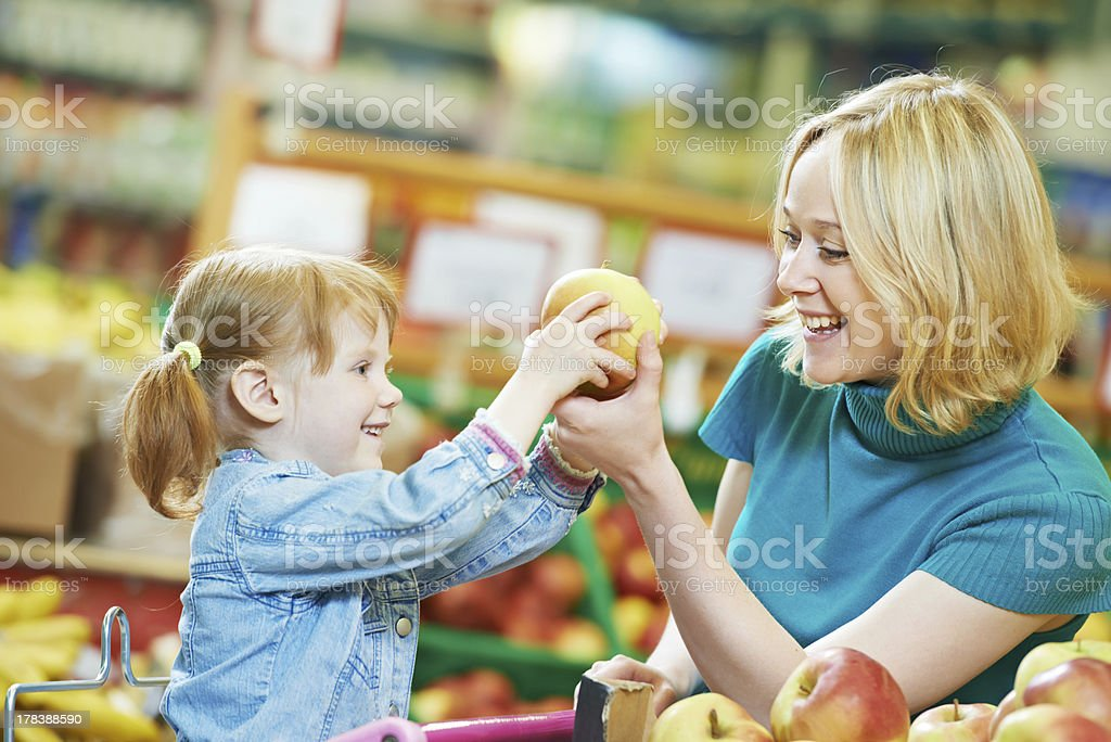 Woman and little girl shopping for fruit at market stock photo