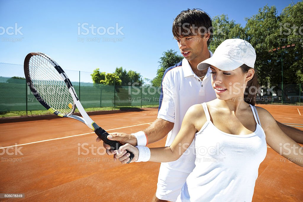 Woman and male tennis instructor practicing stock photo
