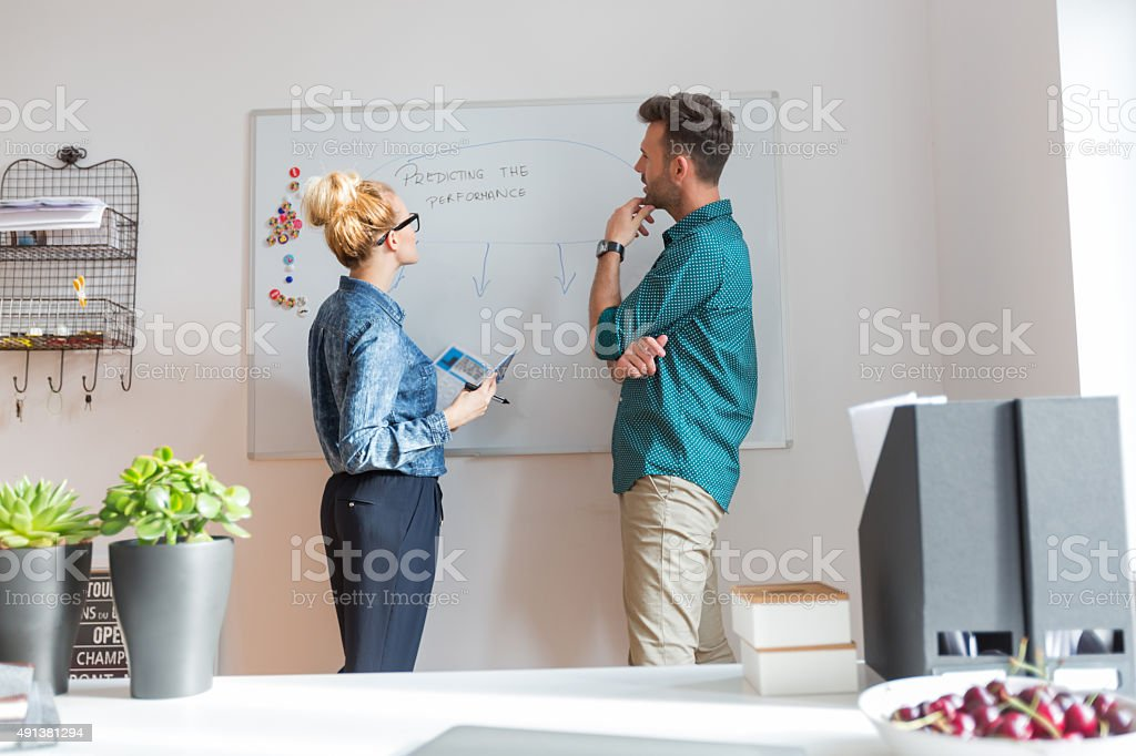Woman and man brainstorming in an office Woman and man standing in front of whiteboard in an office, brainstorming.  2015 Stock Photo