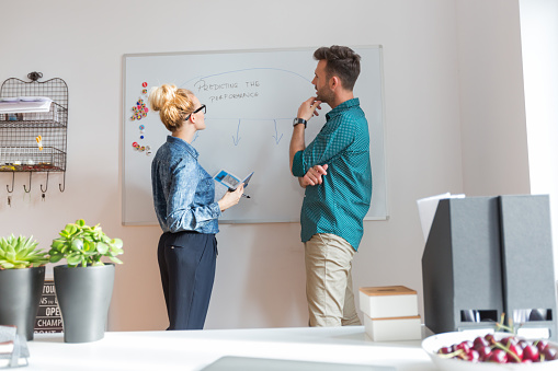 Woman And Man Brainstorming In An Office Stock Photo - Download Image Now