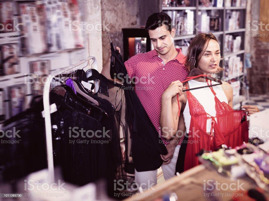 9c4014f74 Mulher e homem compradores escolher cor sensual roupa na loja de sexo foto  royalty-free