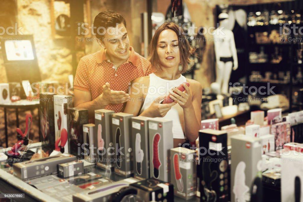 Mulher e homem compradores escolher cor sensual brinquedos na loja de sexo - foto de acervo