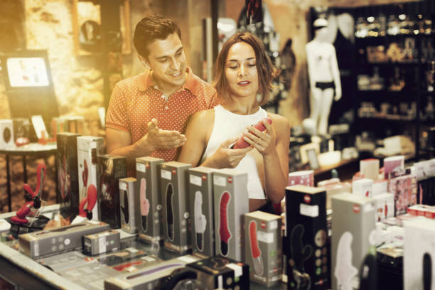 Woman and man buyers choosing color sexy toys in the sex shop Glad happy  smiling couple of woman and man buyers choosing color sexy toys in the sex shop sex toy stock pictures, royalty-free photos & images