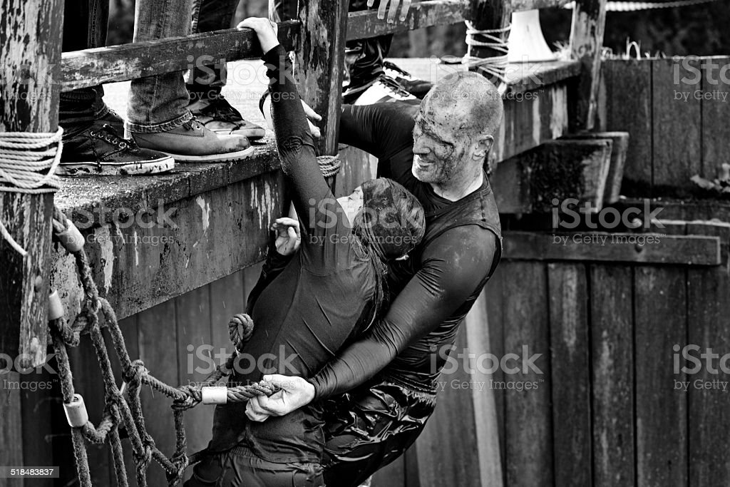 Woman and man climbing an obstacle at mud run event stock photo
