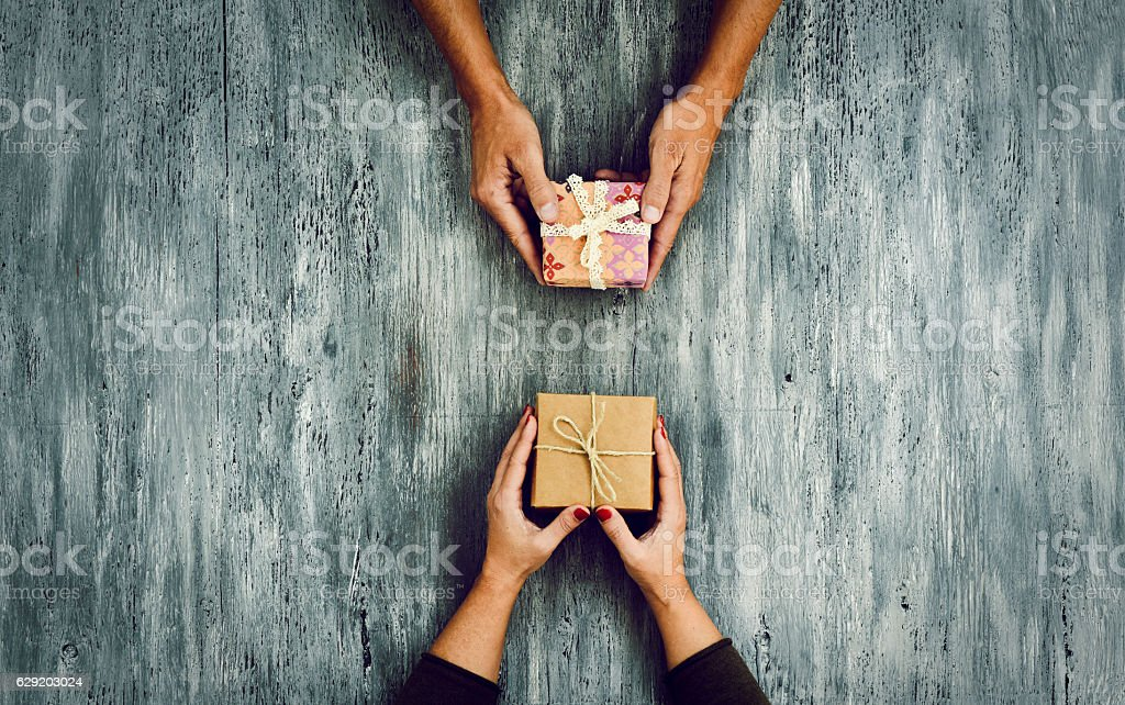 woman and man exchanging gifts - foto de stock