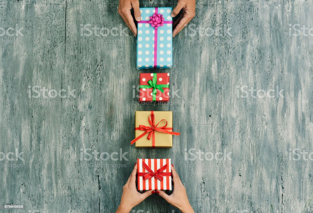 woman and man exchanging gifts stock photo
