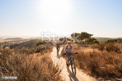 Multi-ethnic daughter and Caucasian father mountain biking in Marina, California, USA.