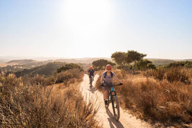 Woman and Man Exploring Single Track Trail on Mountain Bikes stock photo