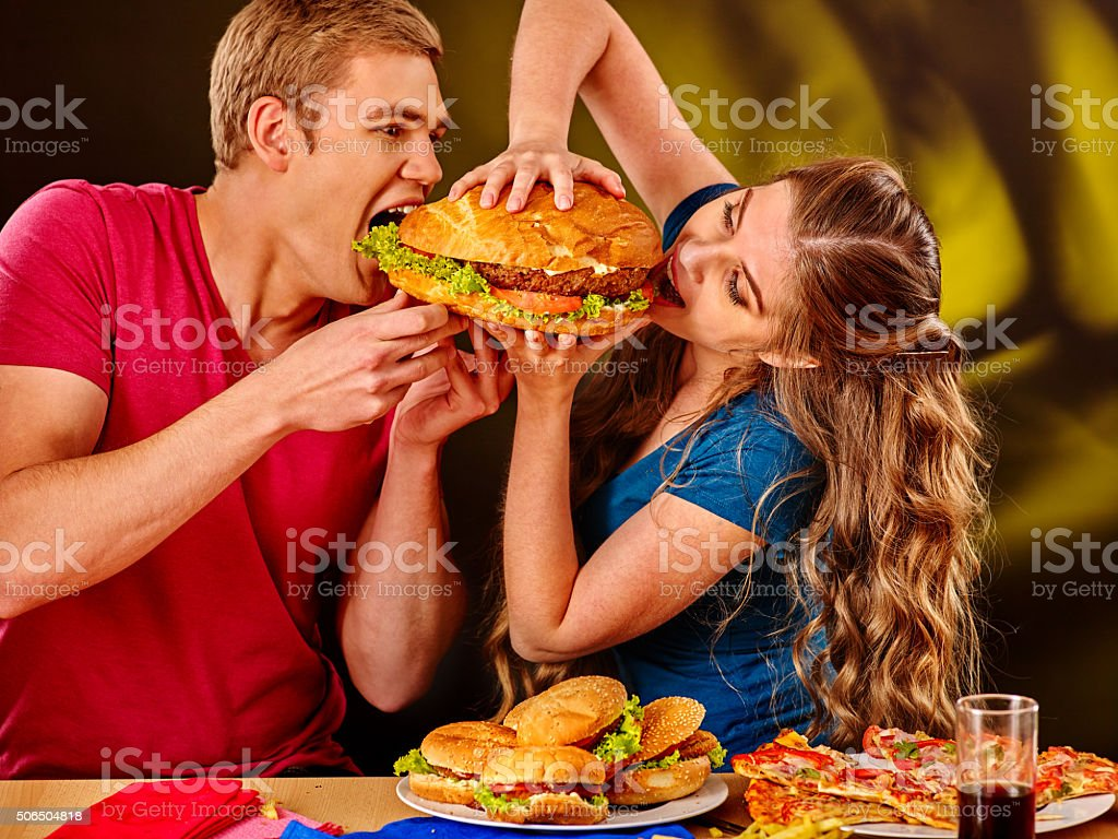 Woman and man feed each other fast food stock photo
