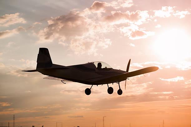 frau und mann fliegen bei sonnenuntergang - flugschule stock-fotos und bilder