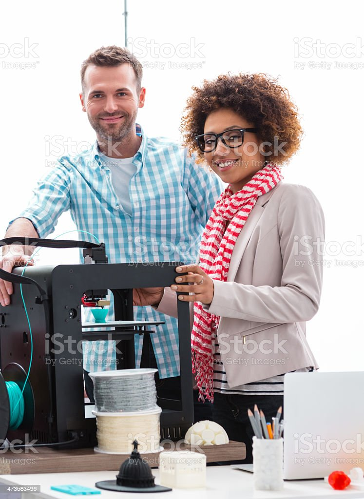 Woman and man in 3D printer office Two business colleagues - afro american woman and caucasian man, working together in a 3d printer office, smiling at camera. 2015 Stock Photo