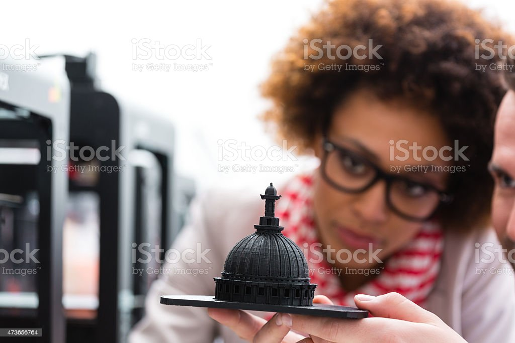 Woman and man in 3D printer office Two business colleagues - afro american woman and caucasian man, working together in a 3d printer office, watching 3d printout. 2015 Stock Photo